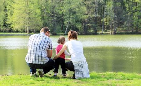 familiy: Happy familiy in the park, having fun near the lake