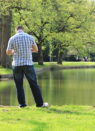 Man is looking at his cell phone in the park  photo
