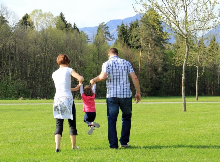 Having fun in the spring park; young child and her parents