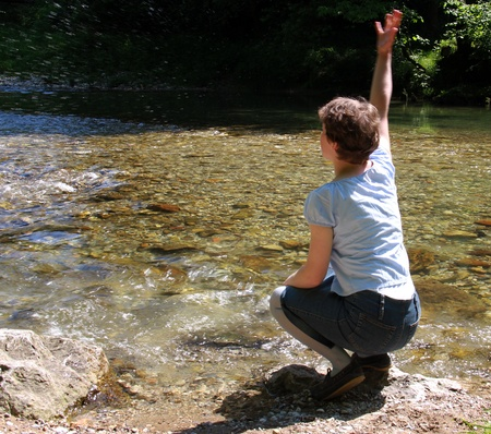 Young woman is splashing water in the river on beautiful spring day  photo