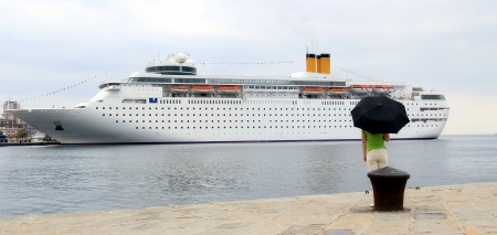 Young woman observing big cruiser in the port  photo