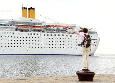 Young woman is waving toward the big cruiser, passing by  photo