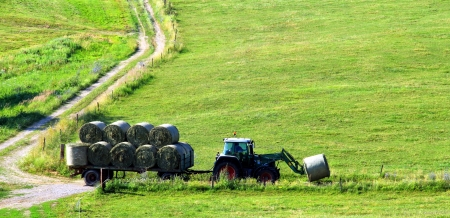 Tractor is pulling trailer with bale  photo