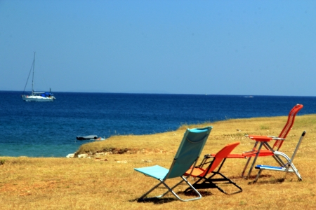 Chairs on the beach and sailing boat  photo