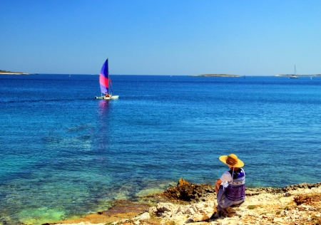gentle dream vacation: Lonely woman on the coast, observing small sailing ship