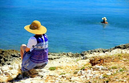 gentle dream vacation: Young woman sitting on the coast, observing the sea and swimmer  Stock Photo