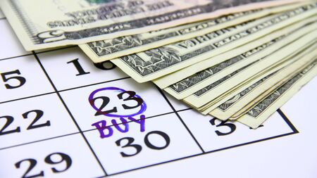 Buying concept with paper money and calendar
