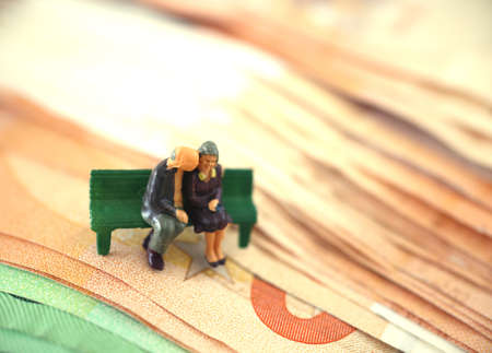 Old couple on a bench. Retired. Pension. Safe in older years. On Euro banknote. Miniature people.