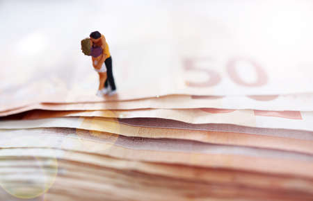 Yoiung couple in love. In a hug. On Euro paper money. Wealthy. Happy. Successful. Miniature people. Imagens