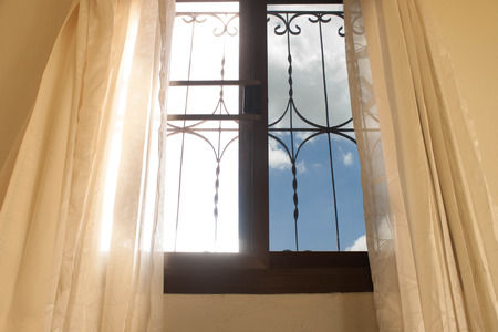 Window with bright light shines  And the other side has a mirror sunglasses And cream curtains photo