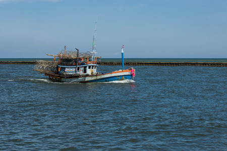 trawl: fishery boat is coming back to the shore in the evening Stock Photo