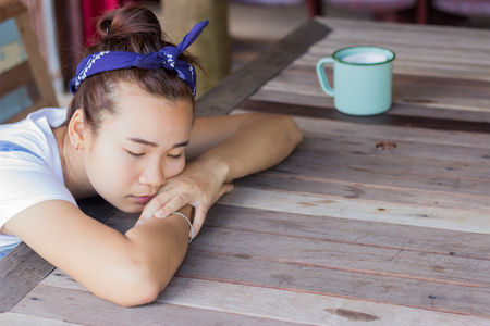 a girl naps beside a  table Stock Photo