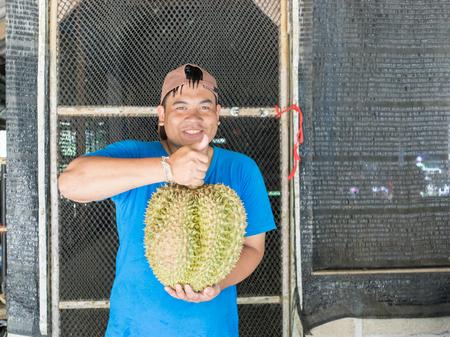 Thai young gardener show his durian from organic garden Stock Photo