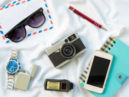 Flat Lay photo with props are Air letter, watch, pen, Flash, Camera, Glasses, Charger, Blue Notebook and smartphone on white fabric background.