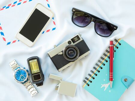 pen tablet: Flat Lay photo with props are Air letter, watch, pen, Flash, Camera, Glasses, Charger, Blue Notebook and smartphone on white fabric background.