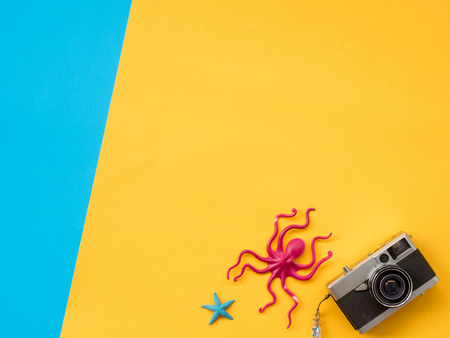 untidy: Summer Background, Summer holiday concept, Travel Concept with Untidy props are Sunscreen, Glasses, Camera, sea animal and hat on blue and yellow background. Stock Photo