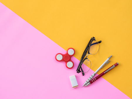 Stationary Background. Flat Lay Photo of Stationary with hand spinner, glasses and stationary on pink and yellow background Stock Photo