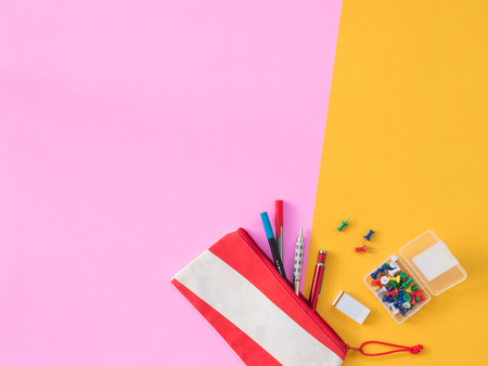 Stationary Background. Flat Lay Photo of Stationary with notebook, pencil, Eraser on the yellow and pink background.