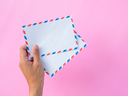 two White envelopes in the hand on pink background Stock Photo