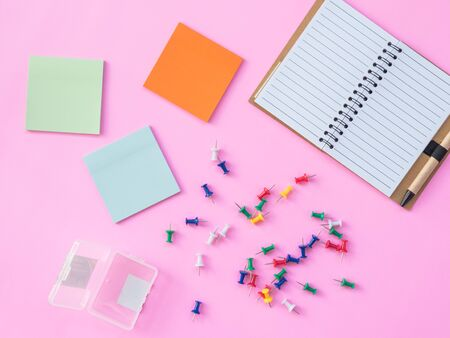 Stationary Background. Flat Lay Photo of Stationary with pin and post it paper and notebook on pink background