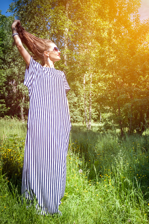 loose hair: Girl holds himself for loose hair standing in a dress on nature Stock Photo