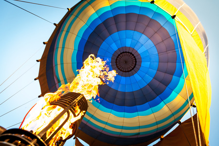 slings: Hot air from a gas burner fills the dome of the balloon