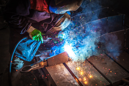 semi automatic: Fantastic sparks during MIG welding of the valve body