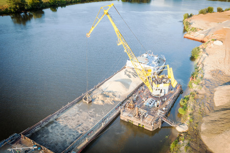 jib: Floating jib crane during loading of sand on barge Stock Photo