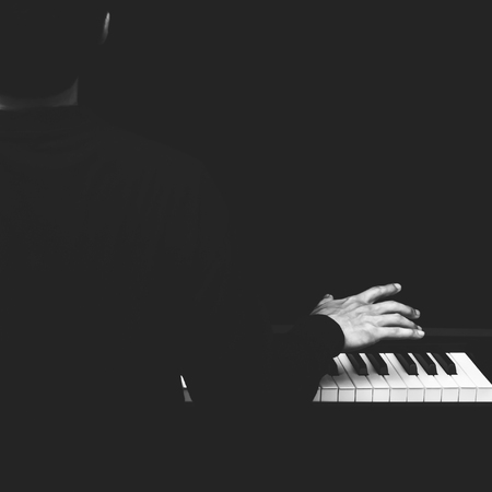 back of male asian musician playing piano, black and white Stock Photo