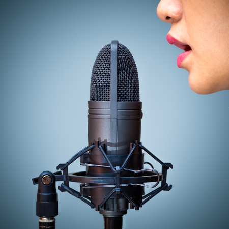 asian female singer mouth singing on microphone, isolated on blue