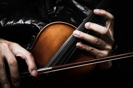 cellos: hands of musician in black jacket posing on classical violin