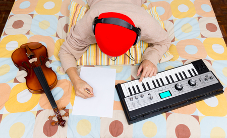 one sheet: asian male composer, musician writing song & playing keyboard on bed