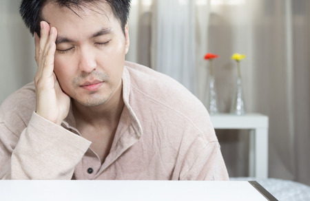 doldrums: asian handsome man feels headache, sick and alone in bedroom