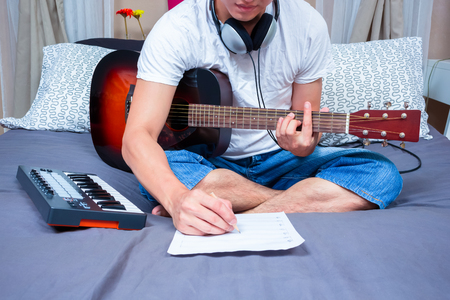 asian male composer, musician writing song & playing guitar on bed