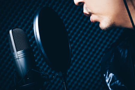 asian singer singing with condenser microphone in recording studio Stock Photo