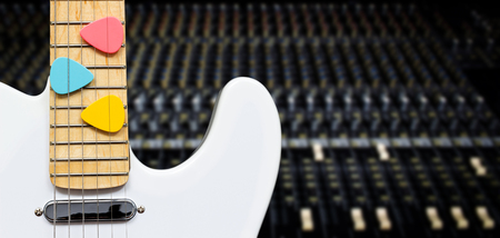 picks: white electric guitar with colorful picks on studio mixer background Stock Photo
