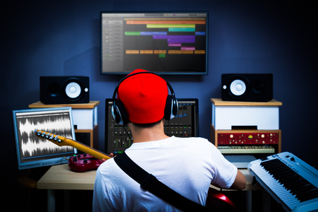 back of male musician playing guitar in recording studio for music background Foto de archivo