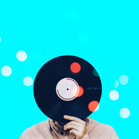 man holding record & colorful bokeh, isolated on blue. art filter, music background