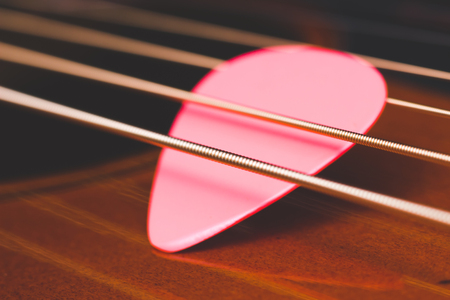 pink pick on acoustic guitar strings, shallow dept of field. music background