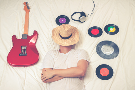 man sleeping on bed with records, headphone and electric guitar. cross process for vintage photo style
