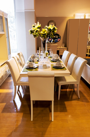 living room design: dining table and comfortable chairs in home with elegant table setting