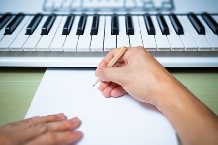 music lyrics: professional composer hands writing songs on blank white paper with studio keyboard & computer Foto de archivo