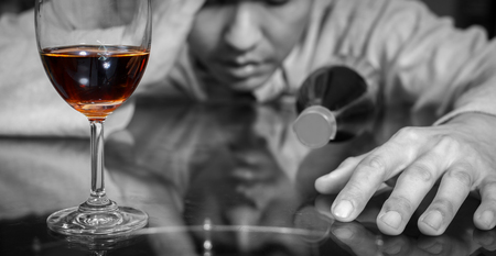 drunk and lonely asian man with wine glass and whiskey bottle, focus on glass