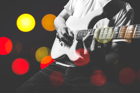 asian musician playing electric guitar with colourful bokeh light on stage