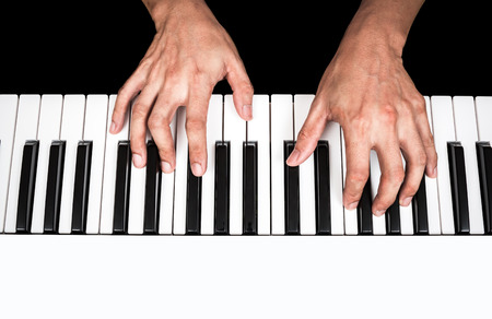 keyboard: professional asian musician hands playing white piano, isolated on black