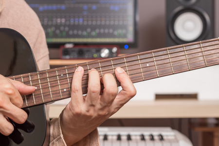 keyboard: musician hands playing acoustic guitar in recording studio