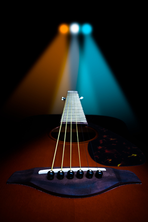 acoustic guitar & colorful spotlight, isolated on black
