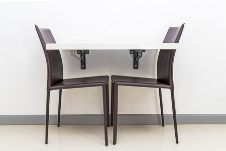 wooden floors: white table, black leather chairs on white wall background for small space interior concept Stock Photo