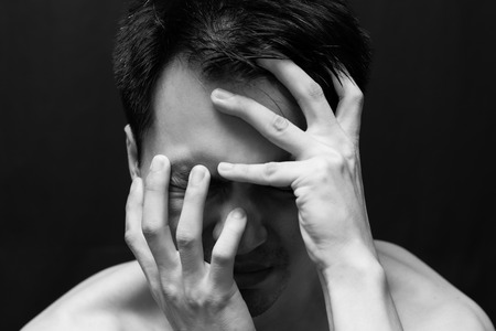 doldrums: asian handsome man in black and white emotion portrait photo  feel sad ,headache and alone on dark background Stock Photo