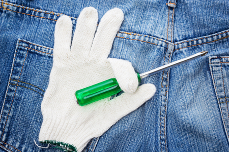 screwdriver on glove, blue jeans background for repair  restore tools DIY concept